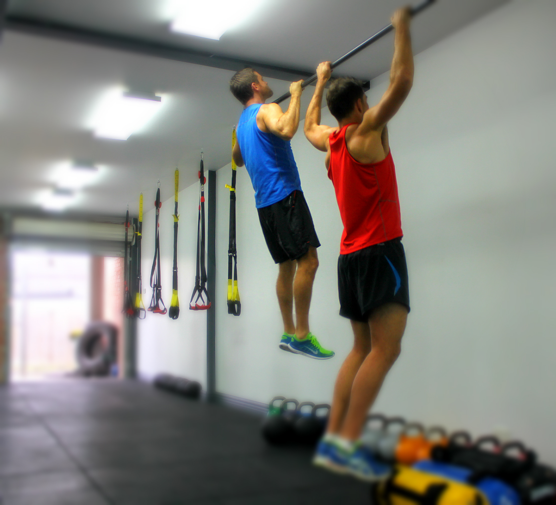 two men performing chin ups/ pull ups
