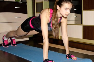 woman in black and pink outfit doing pushup