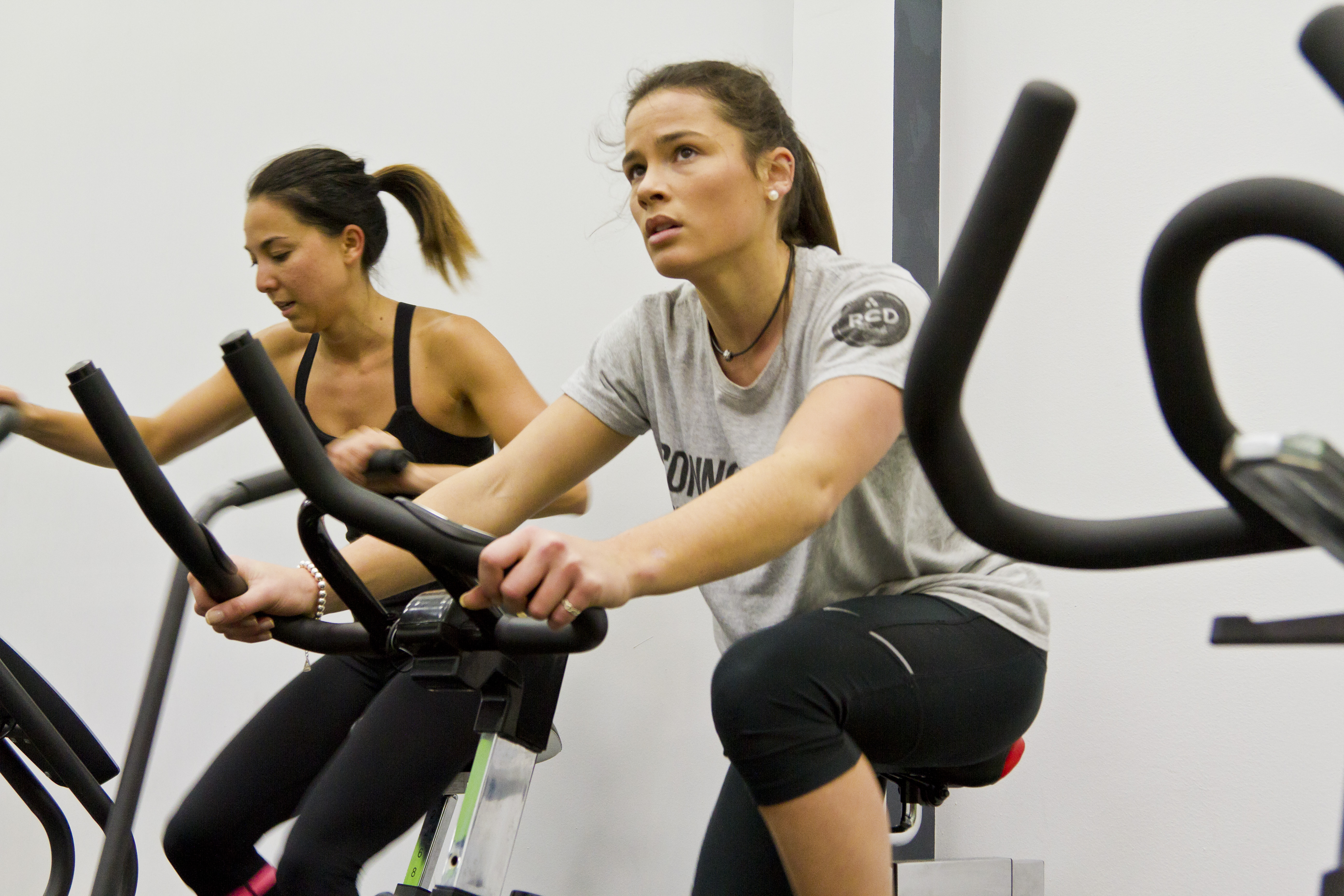 Trifusion fitness two ladies, one on cycle machine and one on stepper