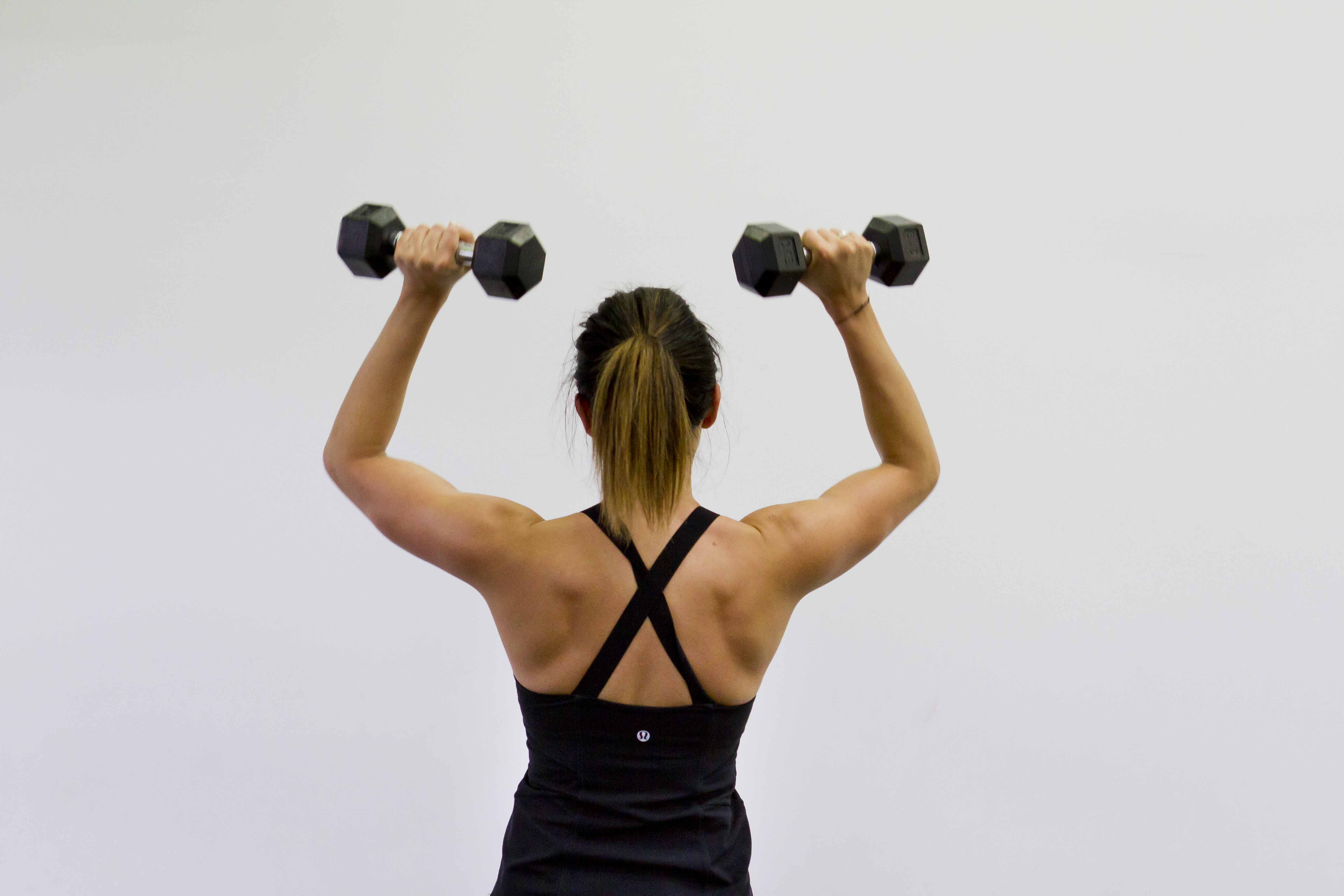 Trifusion fitness lady performing military press with dumbbells