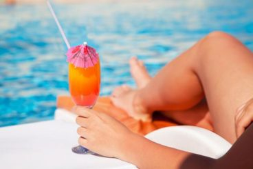 trifusion fitness image of relaxing in sun by pool with cocktail